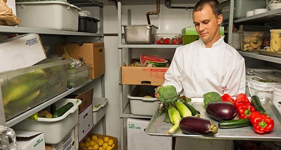Chef selecting vegetables in fridge
